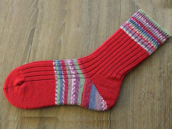 Rode ambachtelijk gebreide sokken met een twist